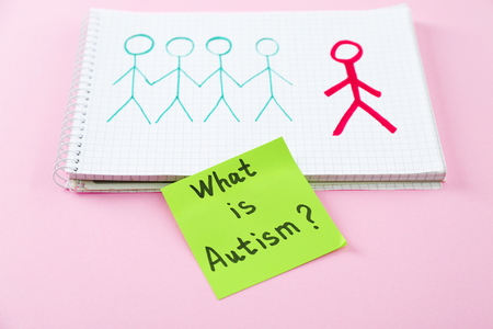 Paper with text WHAT IS AUTISM? and drawing in notebook on color background