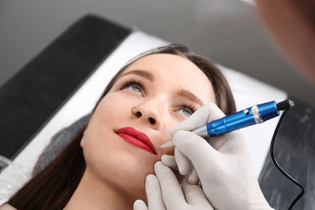 Professional tattoo master applying permanent makeup on lips in salon