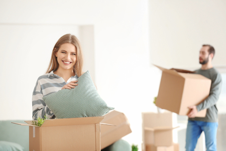 Young woman with moving box in room at new home