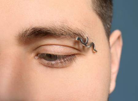 Young man with pierced eyebrow, closeup Stock Photo
