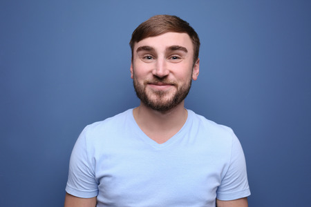 Young man with dyed eyebrows on color background