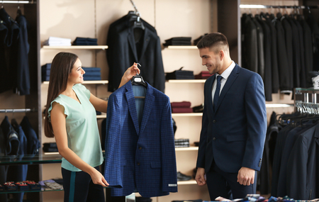 Female shop assistant helping man to choose suit in store 스톡 콘텐츠