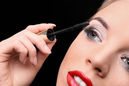 Beautiful young woman with eyelash extensions applying mascara on black background, closeup Stock fotó