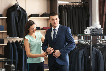 Female shop assistant helping man to choose suit in store 免版税图像