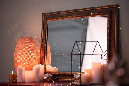 Burning candles and beautiful mirror on table