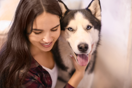 Young woman with cute Husky dog at home. Pet adoption