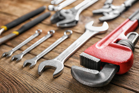 Plumber's tools on wooden background