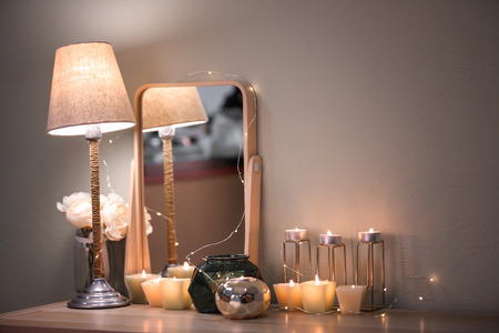 Burning candles and modern mirror on table