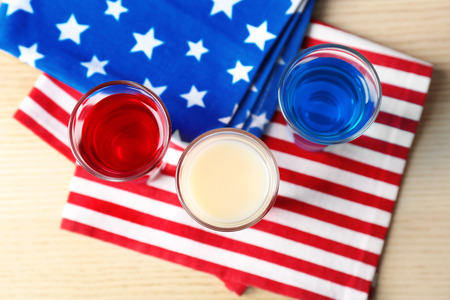 Cocktails in colors of American flag on wooden table