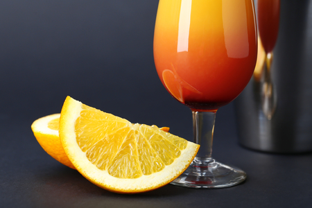 Glass of Sex on the Beach cocktail and orange slices against dark background, closeup Stock Photo