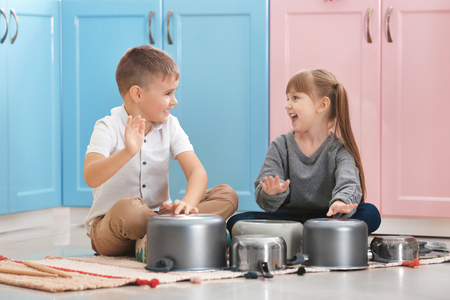 Cute little children playing drums on kitchenware at home