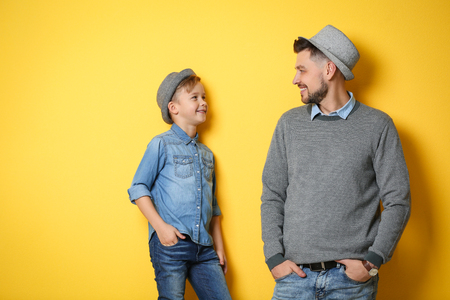 Stylish father and son on color background Stock Photo