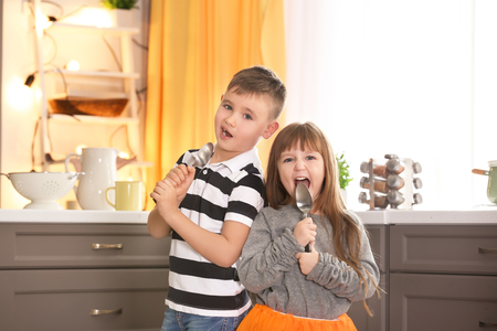 Cute little children using spoons as microphone in kitchen 免版税图像