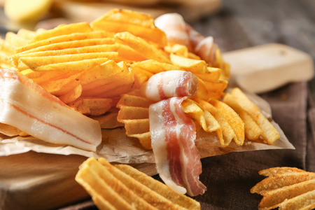 Crispy potato chips with bacon on wooden board, closeup