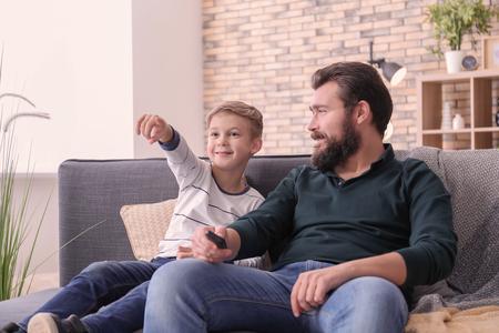 Vater und Sohn schauen gemeinsam zu Hause fern Standard-Bild