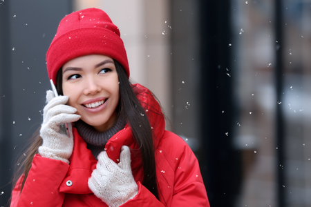 Beautiful young woman talking on mobile phone outdoors on winter day Imagens