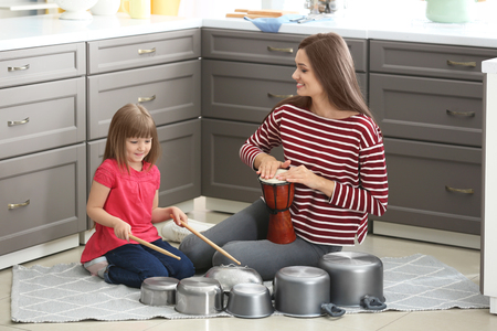 Mother and her daughter playing drums in kitchen Foto de archivo