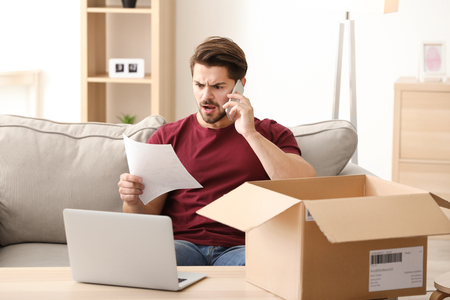 Young man making call about delivered parcel at home Stock Photo