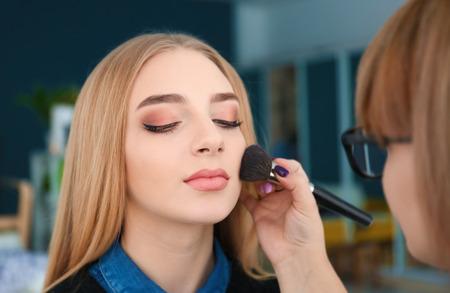 Professional visage artist applying makeup on woman's face backstage Banque d'images