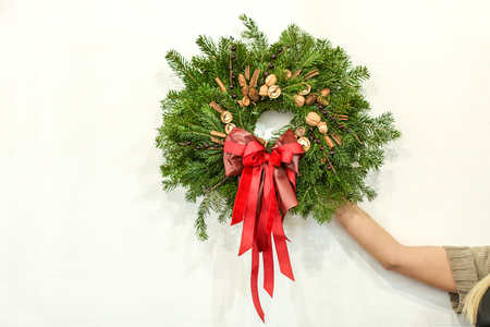 Female florist with Christmas wreath on light wall background