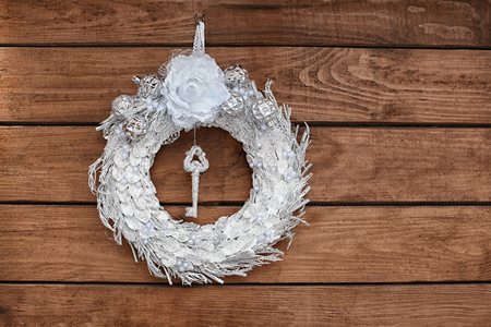 Beautiful Christmas wreath made by professional florist hanging on wooden background Imagens