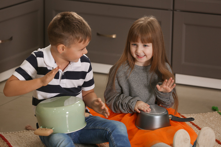 Cute little musicians playing drums on kitchenware at home Reklamní fotografie