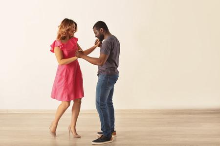 Cute interracial couple dancing in empty room Stock Photo