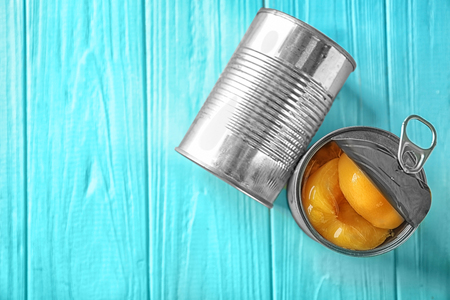 Cans with pickled apricots on wooden background 免版税图像