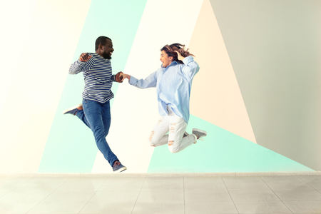 Cute interracial couple jumping against color wall
