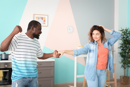 Cute interracial couple dancing at home Stock Photo