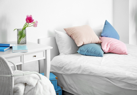 Light room interior with comfortable bed
