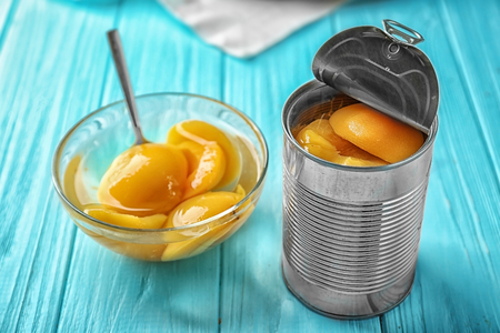 Can and bowl with pickled apricots on table