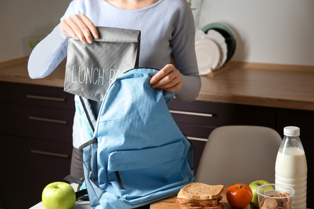 Mother putting school lunch bag with food into backpack at home