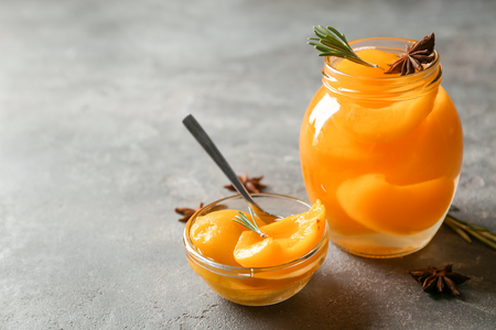 Jar and bowl with pickled apricots on table Banco de Imagens