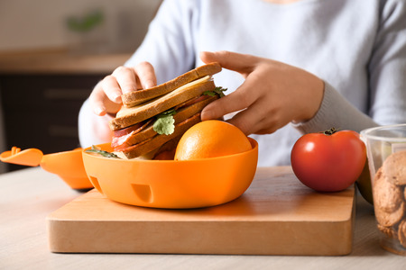 Mother putting food into school lunch box on table Stock Photo
