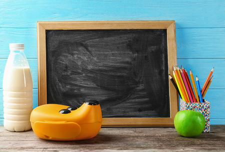 Lunch box with food for schoolchild and blackboard on wooden background