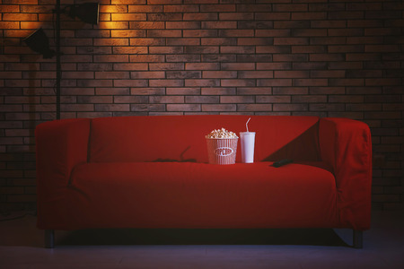 Comfortable couch with popcorn, drink and remote control indoors. Home cinema Imagens