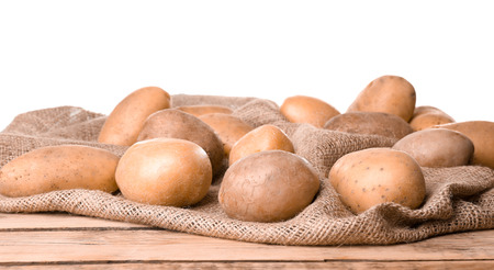 Fresh raw potatoes on wooden table against white background Banco de Imagens