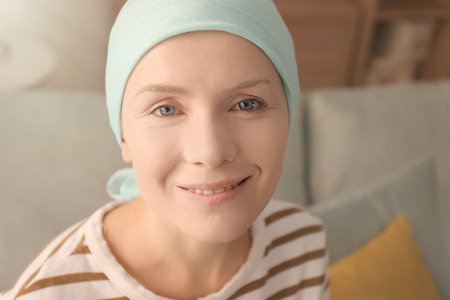 Young woman with cancer in headscarf indoors Stock Photo
