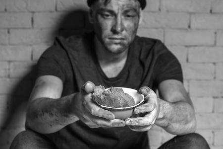 Hombre pobre hambriento sosteniendo un tazón con un pedazo de pan mientras está sentado cerca de la pared de ladrillo Foto de archivo