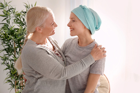 Mature woman visiting her daughter with cancer indoors
