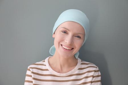 Junge Frau mit Krebs im Kopftuch auf grauem Hintergrund