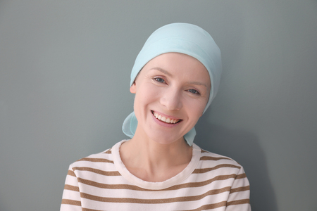 Young woman with cancer in headscarf on grey background Stockfoto