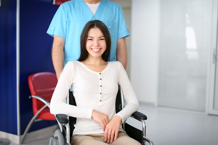 Männlicher Arzt, der sich drinnen um junge Frau im Rollstuhl kümmert
