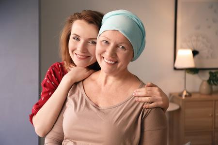 Mujer joven visitando a su madre con cáncer en el interior