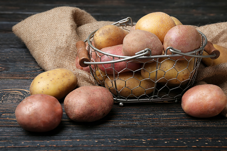 Basket with fresh raw potatoes on wooden table