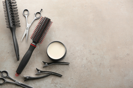 Professional hairdressers tools and clay for hair on grey background