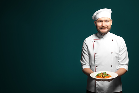 Handsome male chef holding plate with dish on color background Stockfoto