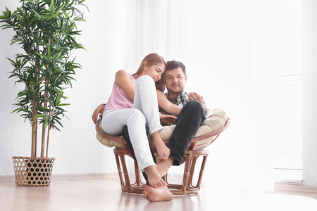 Cute young lovely couple sitting in armchair at home 免版税图像