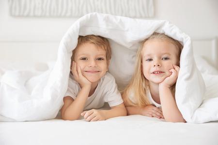 Cute children lying under blanket in bed Banque d'images